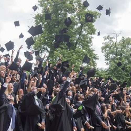 Graduates throwing hats into the air